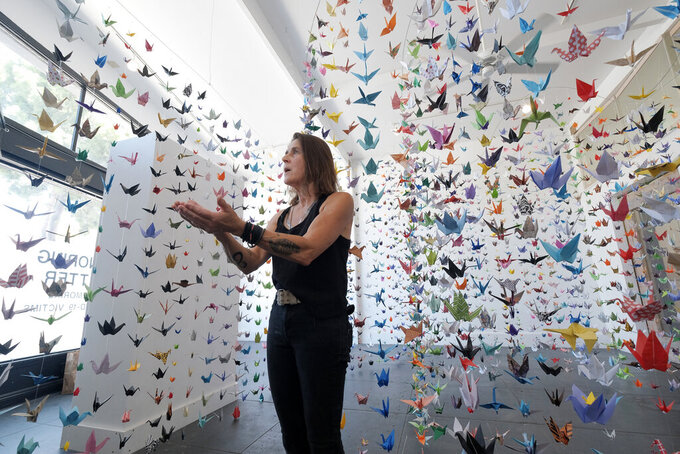 Artist Karla Funderburk, owner of Matter Studio Gallery, talks about the thousands of origami paper cranes hanging in an exhibit honoring the victims of COVID-19, in Los Angeles, Tuesday, Aug. 11, 2020. Funderburk started making the cranes three months earlier, stringing the paper swans in pink, blue, yellow and other colors together and hanging them in her gallery. (AP Photo/Richard Vogel)
