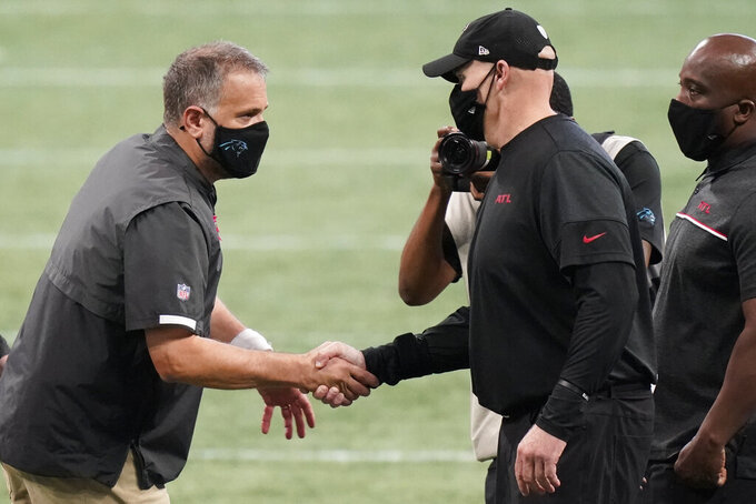 Carolina Panthers head coach Matt Rhule shakes hands with Atlanta Falcons head coach Dan Quinn after an NFL football game, Sunday, Oct. 11, 2020, in Atlanta. (AP Photo/Brynn Anderson)