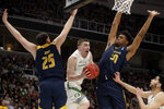 Oregon guard Payton Pritchard, middle, drives to the basket between UC Irvine guard Spencer Rivers, left, and forward Elston Jones during the first half of a second-round game in the NCAA men's college basketball tournament Sunday, March 24, 2019, in San Jose, Calif. (AP Photo/Jeff Chiu)
