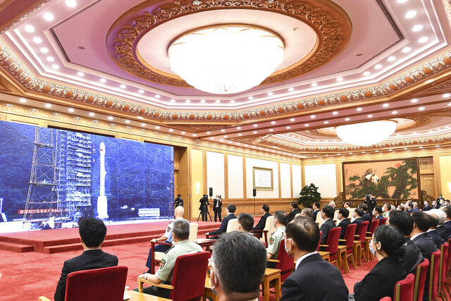 In this photo released by Xinhua News Agency, officials attend the completion and commissioning ceremony for the Beidou Navigation Satellite System (BDS-3) at the Great Hall of the People in Beijing Friday, July 31, 2020. China is celebrating the completion of its BeiDou Navigation Satellite System that could rival the U.S. Global Positioning System and significantly boost China's security and geopolitical clout. (Yan Yan/Xinhua via AP)