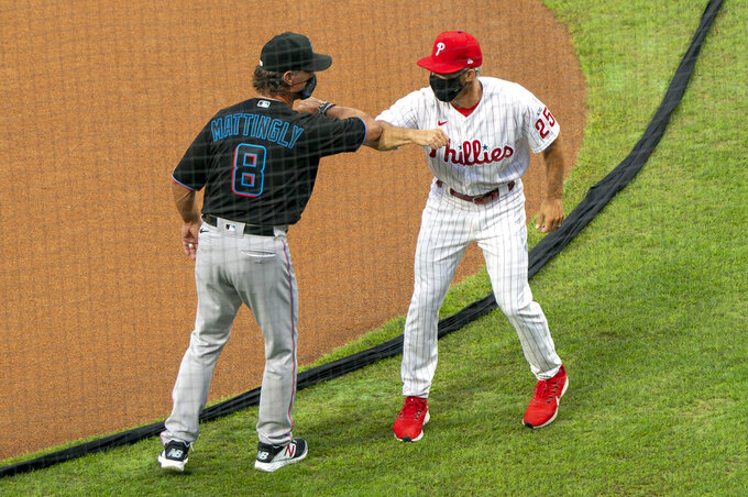 FILE - In this July 24, 2020, file photo, Miami Marlins manager Don Mattingly, left, gives an elbow-bump to Philadelphia Phillies manager Joe Girardi, right, prior to a baseball game in Philadelphia. Mattingly won the NL Manager of the Year award on Tuesday night, Nov. 10. Mattingly guided the Marlins to their first playoff appearance since 2003 despite dealing with a COVID-19 outbreak that paused their season and ravaged the roster. (AP Photo/Chris Szagola, File)