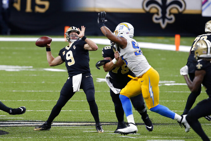 New Orleans Saints quarterback Drew Brees (9) throws a touchdown pass to tight end Jared Cook, not pictured, under pressure from Los Angeles Chargers defensive tackle Jerry Tillery (99) in the second half of an NFL football game in New Orleans, Monday, Oct. 12, 2020. (AP Photo/Butch Dill)