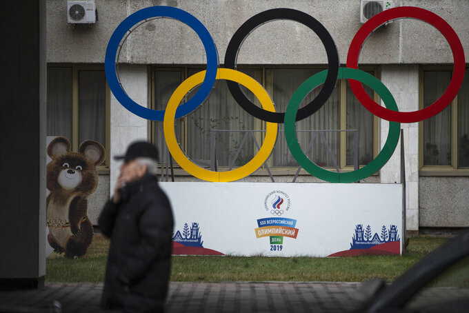 FILE - In this Nov. 28, 2019 file photo Olympic Rings and a model of Misha the Bear Cub, the mascot of the Moscow 1980 Olympic Games, left, are seen in the yard of Russian Olympic Committee building in Moscow, Russia. A U.S. government study concludes that Americans do not get their money's worth out of the $2.7 million that Congress sent to the World Anti-Doping Agency this year. The report from the White House Office of National Drug Control Policy concludes that the U.S. is under-represented on WADA's key policymaking committees. It says WADA has not moved quickly or far enough to reform itself in the wake of the Russian doping scandal.  (AP Photo/Pavel Golovkin, file)