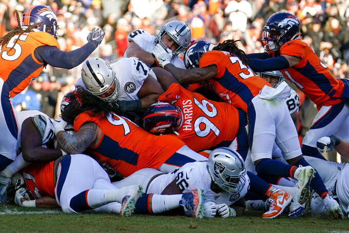 Oakland Raiders running back Alec Ingold, above center, is stopped before the goal line during the first half of an NFL football game against the Denver Broncos, Sunday, Dec. 29, 2019, in Denver. (AP Photo/Jack Dempsey)