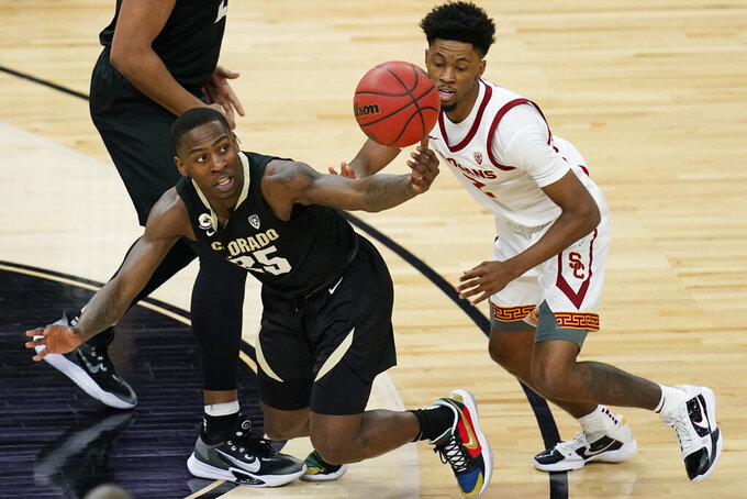 Colorado's McKinley Wright IV, left, and Southern California's Tahj Eaddy (2) vie for the ball during the first half of an NCAA college basketball game in the semifinal round of the Pac-12 men's tournament Friday, March 12, 2021, in Las Vegas. (AP Photo/John Locher)