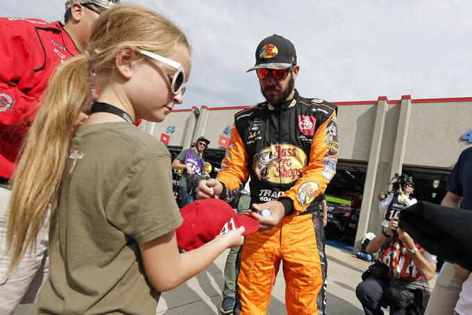 Martin Truex Jr. signs autographs for fans during practice prior to Sunday's NASCAR Cup Series auto race at Charlotte Motor Speedway in Concord, N.C., Saturday, Sept. 28, 2019. (AP Photo/Gerry Broome)
