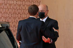Iraqi President Barham Salih, rear, welcomes French President Emmanuel Macron as he arrives at the Baghdad's Presidential Palace, Saturday, Aug. 28, 2021. (AP Photo/Khalid Mohammed)