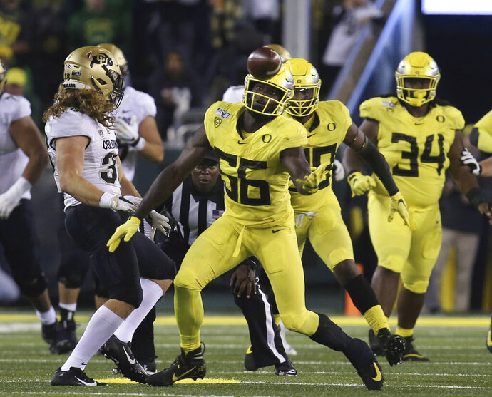 Oregon's Bryson Young, center, intercepts a tipped pass intended for Colorado's Brady Russell, left, during the third quarter of an NCAA college football game Friday, Oct. 11, 2019, in Eugene, Ore. (AP Photo/Chris Pietsch)