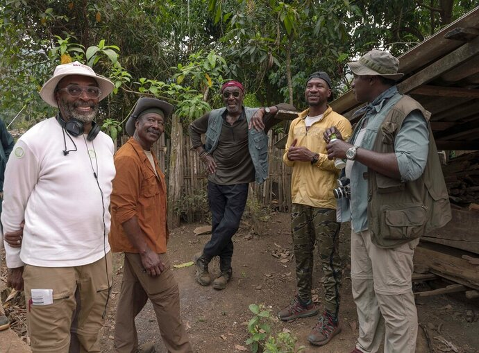 This image released by Netflix shows, from left, filmmaker Spike Lee, from left, with Clarke Peters, Delroy Lindo, Jonathan Majors and Norm Lewis on the set of
