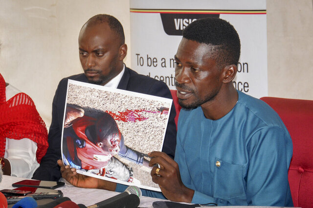 Ugandan opposition presidential candidate Bobi Wine shows a photograph depicting a victim of recent electoral-related violence in the country, at the Electoral Commission in Kampala, Uganda Wednesday, Dec. 2, 2020. Wine said Wednesday after meeting the head of the country's electoral body that he would resume his campaign after suspending it in protest over police brutality after police shot his car tires and fired rubber bullets that injured his bodyguards and supporters. (AP Photo/Ronald Kabuubi)