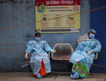 Health workers take rest while waiting to collect nasal swab samples to test for COVID-19 in Hyderabad, India, Tuesday, Sept. 22, 2020. The nation of 1.3 billion people is expected to become the coronavirus pandemic's worst-hit country within weeks, surpassing the United States. (AP Photo/Mahesh Kumar A.)