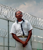 """FILE - In this May 24, 1999 file photo, convicted killer Wayne Williams poses along the fence line at Valdosta Sate Prison, Valdosta, Ga. Atlanta's mayor and chief of police are leading a push to re-examine evidence from a string of murders from 1979 to 1981 that terrorized the city's black community. Mayor Keisha Lance Bottoms and Police Chief Erika Shields announced Thursday, March 21, 2019, that the Georgia Bureau of Investigation will review evidence in the so-called """"Atlanta Child Murders"""" to see if any could be used for further testing. Williams was given two life sentences in 1982 for convictions in the deaths of two adults, thought to be among 29 black children and young adults killed. (AP Photo/John Bazemore, File)"""