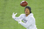 File-This March 31, 2021, file photo shows LSU wide receiver Ja'Marr Chase catching during a drill at an NFL Pro Day at LSU in Baton Rouge, La. Caleb Farley of Virginia Tech was the first top prospect to make the decision that has added a whole new layer of uncertainty to the annual crapshoot that is the NFL draft. Farley had plenty of players follow his lead, including several others set to be high draft picks next week like LSU receiver Chase, Oregon tackle Penei Sewell, Northwestern tackle Rashawn Slater and Penn State linebacker Micah Parsons. (AP Photo/Matthew Hinton, File)
