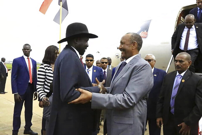 In this photo provided by the official SUNA news agency, Gen. Abdel-Fattah Burhan, center right, head of Sudan's sovereign council, is greeted by South Sudan's President Salva Kiir, center left, in Juba, South Sudan, Monday, Oct. 14, 2019. Sudan's new transitional government is starting talks Monday with rebel leaders in South Sudan's capital, Juba to kick off peace talks aimed at ending the country's yearslong civil wars. Achieving peace is crucial to the transitional government in Sudan. It has counted on ending the wars with rebels in order to revive the country's battered economy through slashing the military spending, which takes up much of the national budget. (SUNA via AP)