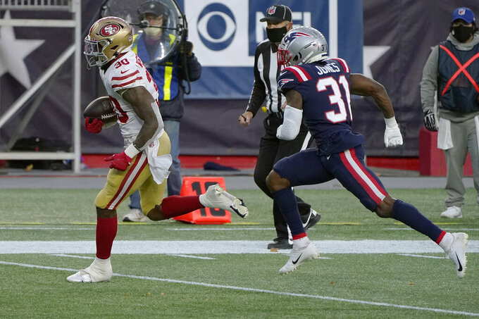 San Francisco 49ers running back Jeff Wilson Jr., left, runs from New England Patriots defensive back Jonathan Jones (31) on his way to a touchdown in the first half of an NFL football game, Sunday, Oct. 25, 2020, in Foxborough, Mass. (AP Photo/Steven Senne)