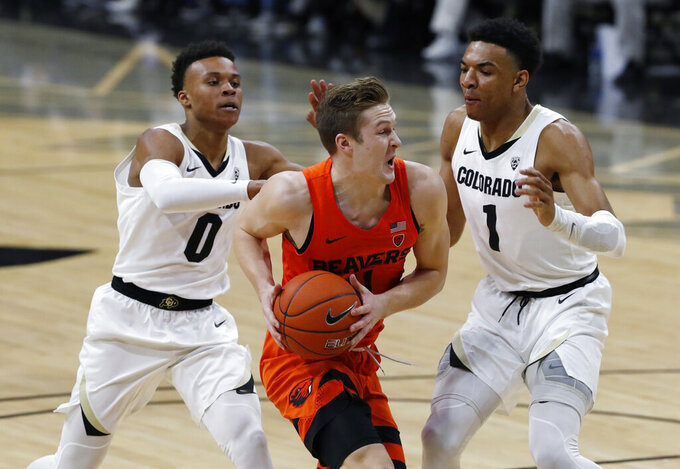 Oregon State guard Zach Reichle, center, drives to the rim past Colorado guards Shane Gatling, left, and Tyler Bey in the first half of an NCAA college basketball game Thursday, Jan. 31, 2019, in Boulder, Colo. (AP Photo/David Zalubowski)