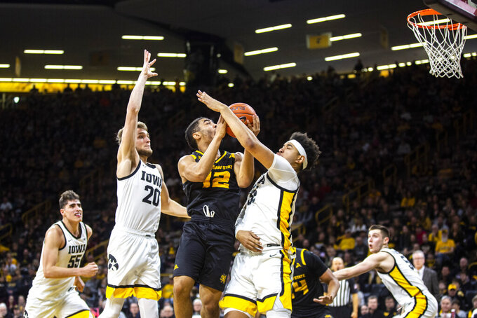 Iowa forwards Cordell Pemsl, right, and Riley Till (20) defend against Kennesaw State guard Jamie Lewis (12) who drives to the basket during an NCAA college college basketball game, Sunday, Dec. 29, 2019, in Iowa City, Iowa. (Joseph Cress/Iowa City Press-Citizen via AP)