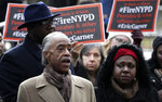 Rev. Al Sharpton, left, stands with activists while speaking during a news conference outside of New York Police headquarters, Thursday, Dec. 6, 2018, in New York.  Daniel Pantaleo, a New York City police officer accused in the 2014 chokehold death of Eric Garner, an unarmed black man, will face a disciplinary trial in May. (AP Photo/Julio Cortez)