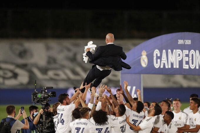 El técnico del Real Madrid, Zinedine Zidane, es lanzado por los aires por sus jugadores, tras la conquista del título de La Liga, el jueves 16 de julio de 2020, con una victoria sobre el Villarreal (AP Foto/Bernat Armangue)