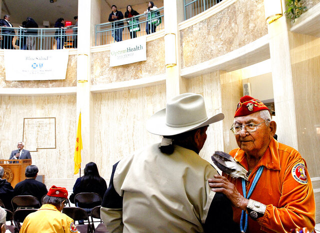 FILE - In this Feb. 4, 2011, file photo, Leland Anthony, Arizona Rep. for Indian Health Incorp., left, speaks with Navajo code talker Joe Vandever Sr. during Native American Day at the roundhouse in Santa Fe, New Mexico. One of the few remaining Navajo Code Talkers who used their native language to confound the Japanese in World War II has died. Joe Vandever Sr. died of health complications Friday, Jan. 31, 2020, in Haystack, New Mexico, west of Grants, according to his family. He was 96. Tribal leaders called Vandever a