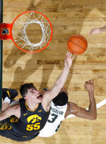 Iowa's Luka Garza, left, reaches for a rebound over Michigan State's Xavier Tillman during the second half of an NCAA college basketball game, Tuesday, Feb. 25, 2020, in East Lansing, Mich. Michigan State won 78-70. (AP Photo/Al Goldis)
