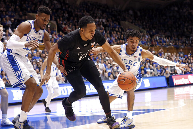 Duke forward Javin DeLaurier, lwft, and guard Tre Jones (3) pressure Miami center Rodney Miller Jr. during the first half of an NCAA college basketball game in Durham, N.C., Tuesday, Jan. 21, 2020. (AP Photo/Gerry Broome)
