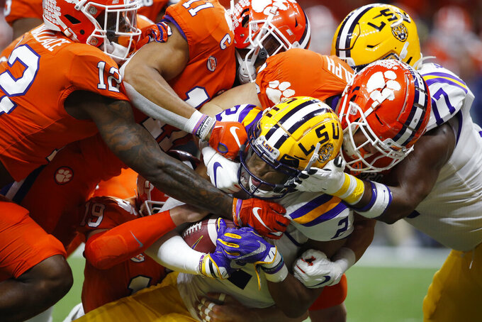 FILE - In this Jan. 13, 2020, file photo, LSU wide receiver Justin Jefferson (2) is tackled by Clemson during the first half of an NCAA College Football Playoff national championship game in New Orleans. The NCAA's latest guidance for playing college sports during the COVID-19 pandemic recommends testing players once a week within 72 hours of competition. For typical Saturday football games, that means Wednesday would be the soonest athletes would be tested. Is that enough for a team of about 100 athletes playing a contact sport to get through a season without major disruptions? Especially, considering simply being exposed to someone who tests positive can land an athlete in quarantine for two weeks? (AP Photo/Gerald Herbert, File)