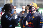 Mercedes driver Lewis Hamilton of Britain, left, talks with Red Bull driver Max Verstappen of the Netherlands after clocking the fastest time in the qualifying for the Spanish Formula One Grand Prix at the Barcelona Catalunya racetrack in Montmelo, just outside Barcelona, Spain, Saturday, May 8, 2021. The Spanish Grand Prix will be held on Sunday. Verstappen clocked the second fastest time. (AP Photo/Emilio Morenatti, Pool)