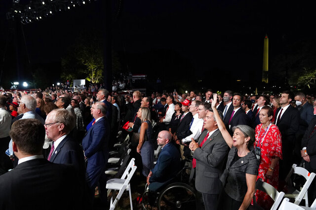 With the Washington Monument in the background, a crowd on the South Lawn of the White House watches the Republican National Convention as it plays on a screen on the fourth day of the convention, Thursday, Aug. 27, 2020, in Washington. (AP Photo/Alex Brandon)