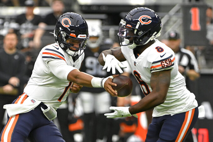 Chicago Bears quarterback Justin Fields (1) hands off to Chicago Bears running back Damien Williams (8) against the Las Vegas Raiders during the first half of an NFL football game, Sunday, Oct. 10, 2021, in Las Vegas. (AP Photo/David Becker)