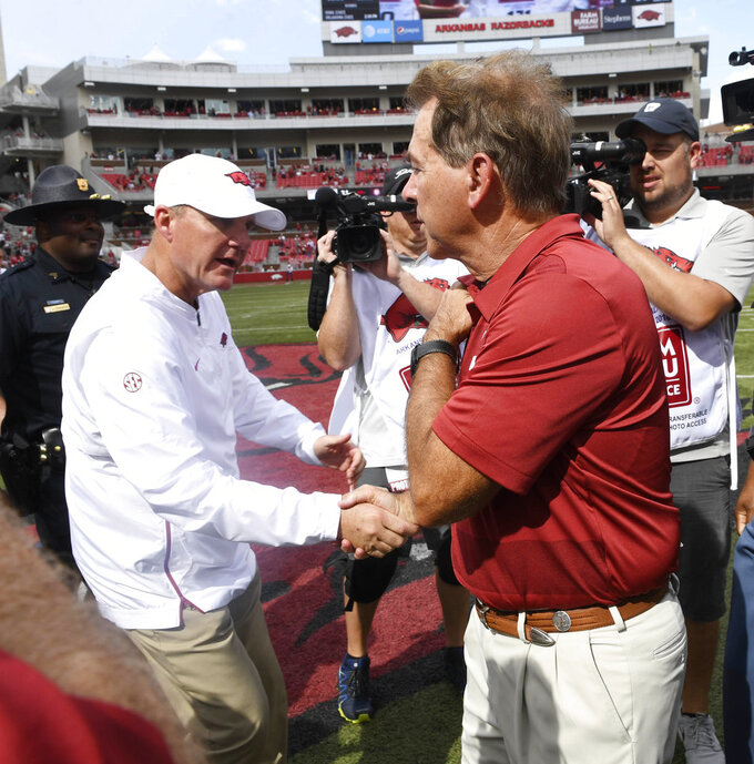 Alabama coach Nick Saban, right, shakes hands with Arkansas coach Chad Morris after Alabama's 65-31 win in an NCAA college football game Saturday, Oct. 6, 2018, in Fayetteville, Ark. (AP Photo/Michael Woods)
