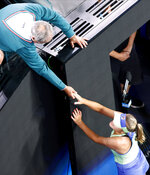 Alex Kenin, left, congratulates his daughter Sofia Kenin of the U.S. after defeating Spain's Garbine Muguruza in the women's singles final at the Australian Open tennis championship in Melbourne, Australia, Saturday, Feb. 1, 2020. (AP Photo/Andy Wong)