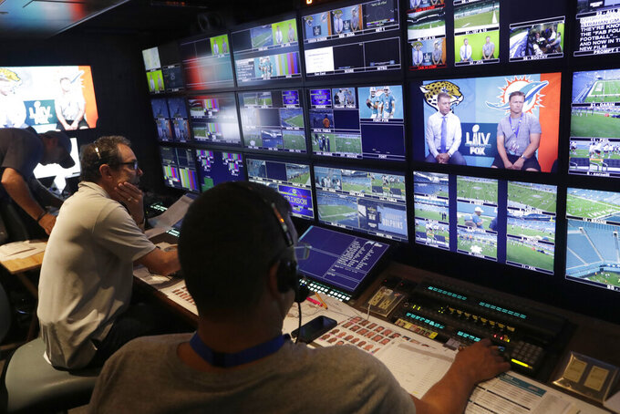 In this Friday, Aug. 23, 2019, photo, Richie Zyontz, producer of Fox Sports, left, works in the Fox TV truck before a preseason NFL football game between the Miami Dolphins and Jacksonville Jaguars, in Miami Gardens, Fla. The exhibition game served as a dress rehearsal for the Fox Sports crew for the upcoming Super Bowl to be hosted by Miami in 2020. (AP Photo/Lynne Sladky)