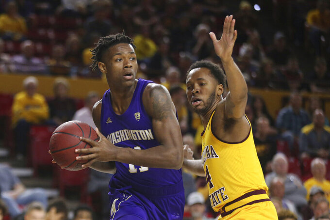Washington's Nahziah Carter (11) is defended by Arizona State's Kimani Lawrence (4) during the first half of an NCAA college basketball game Thursday, March 5, 2020, in Tempe, Ariz. (AP Photo/Darryl Webb)