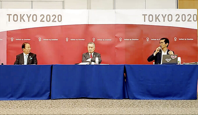 In this image made from video provided by Tokyo 2020 Official YouTube Channel, Tokyo 2020 Olympics President Yoshiro Mori, center, with CEO Toshiro Muto, left, attends a press conference after an IOC executive board meeting in Tokyo, Wednesday, June 10, 2020. (Tokyo 2020 Official YouTube Channel via AP)