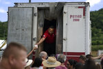 Residents receive aid supplies after suffering the previous day's magnitude 6.4 quake in Yauco, Puerto Rico, Wednesday, Jan. 8, 2020. More than 250,000 The quake that struck before dawn on Tuesday killed one person, injured nine others and knocked out power across the U.S. territory. More than 250,000 Puerto Ricans remained without water and another half a million without power, which also affected telecommunications. (AP Photo/Carlos Giusti)