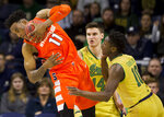 Syracuse's Oshae Brissett (11) grabs a rebound over Notre Dame's Nate Laszewski (14) and T.J. Gibbs Jr. (10) during the second half of an NCAA college basketball game Saturday, Jan. 5, 2019, in South Bend, Ind. Syracuse won 72-62. (AP Photo/Robert Franklin)
