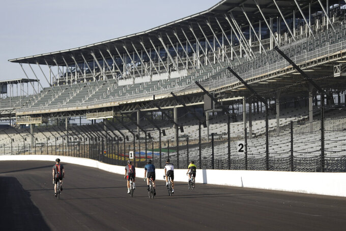IndyCar drivers Charlie Kimball, Dalton Kellett, Spencer Pigot, Felix Rosenqvist and Marcus Ericsson rides their bicycles down the main straightaway at Indianapolis Motor Speedway, Sunday, May 24, 2020, in Indianapolis. The Indianapolis 500 was postponed because of the coronavirus pandemic. The race will instead be held Aug. 23, three months later than its May 24 scheduled date. (AP Photo/Darron Cummings)