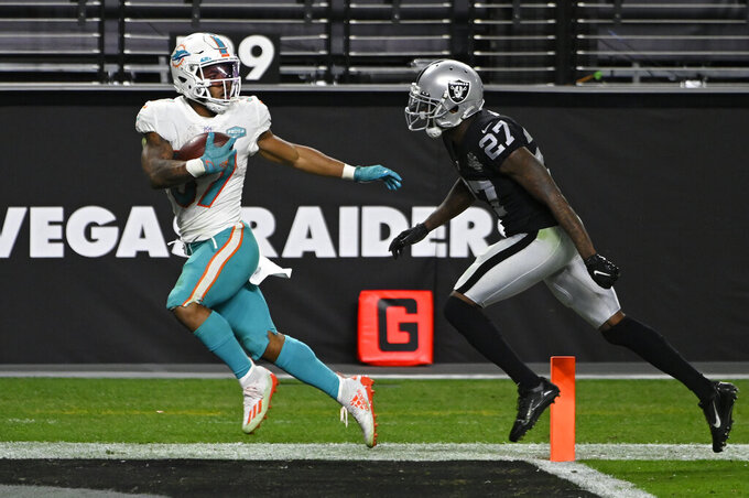 Miami Dolphins running back Myles Gaskin (37) scores a touchdown against Las Vegas Raiders cornerback Trayvon Mullen (27) during the second half of an NFL football game, Saturday, Dec. 26, 2020, in Las Vegas. (AP Photo/David Becker)