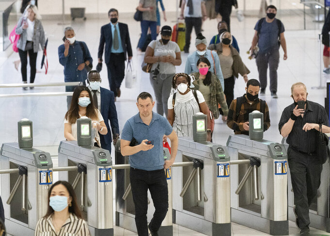 People commute through the World Trade Center, Friday, July 9, 2021, in New York. Businesses that have announced vaccine mandates say some workers who had been on the fence have since gotten inoculated against COVID-19. But many holdouts remain, a likely sign of what is to come once a federal mandate goes into effect. (AP Photo/Mark Lennihan)