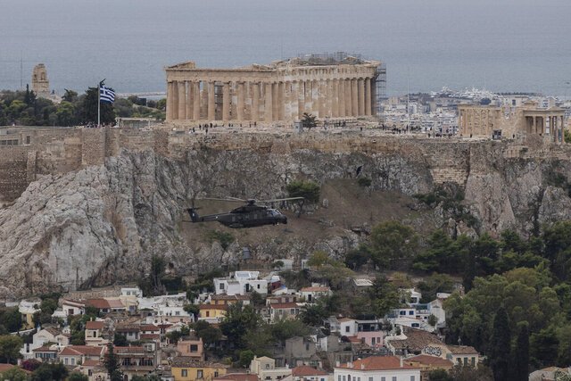 A military helicopter flies in front of the Parthenon temple on the ancient Acropolis hill in Athens, Wednesday Oct. 28, 2020 during a national holiday . The helicopters fly next to Acropolis hill to celebrate Greece's refusal to align itself with a belligerent fascist Italy in 1940 and instead fight a much stronger opponent, a decision which dragged it into World War II and eventually led to a brutal occupation by Nazi Germany.(AP Photo/ Petros Giannakouris)