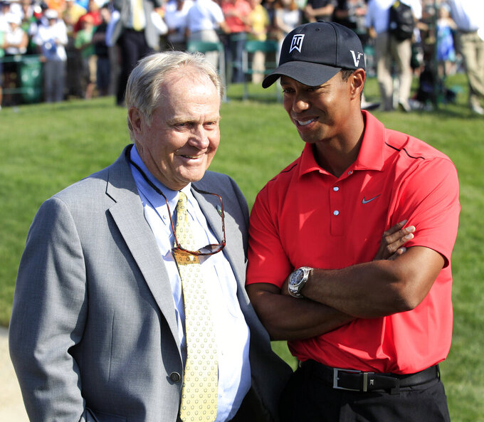 FILE - In this June 3, 2012, file photo, Jack Nicklaus, left, talks with Tiger Woods after Woods won the Memorial golf tournament at the Muirfield Village Golf Club in Dublin, Ohio. The PGA Tour has a deal that would bring a one-time event to Muirfield Village a week before the Memorial, giving it tournaments in consecutive weeks.  (AP Photo/Tony Dejak, File)