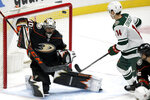 Anaheim Ducks goaltender Ryan Mille, left, blocks a a shot against Minnesota Wild center Joel Eriksson Ek during the first period of an NHL hockey game in Anaheim, Calif., Wednesday, Jan. 20, 2021. (AP Photo/Alex Gallardo)
