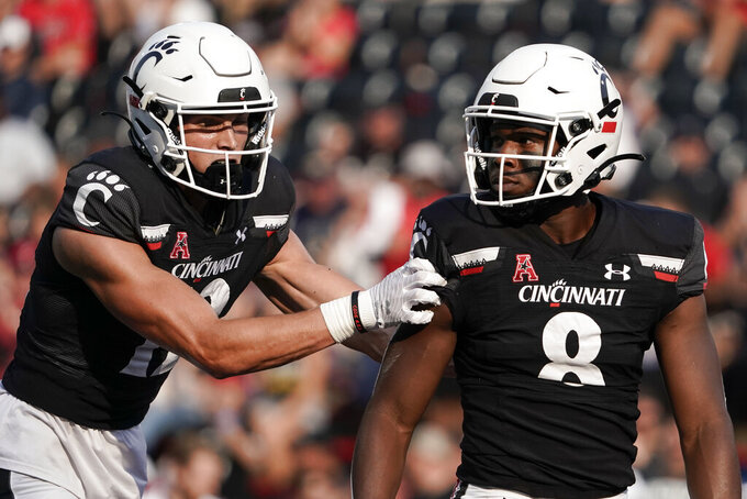 Cincinnati wide receiver Alec Pierce, left, reacts after wide receiver Michael Young Jr. (8) made a catch during the second half of an NCAA college football game against Murray State, Saturday, Sept. 11, 2021, in Cincinnati. (AP Photo/Jeff Dean)