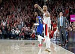 Portland Trail Blazers guard Damian Lillard, right, looks to the Denver Nuggets bench after making a three point basket during the second half of Game 3 of an NBA basketball second-round playoff series Friday, May 3, 2019, in Portland, Ore. (AP Photo/Craig Mitchelldyer)