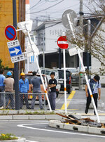 In this Sunday, Sept. 22, 2019, photo, road signs lean after strong winds brought about by Typhoon Tapah swept Nobeoka, Miyazaki prefecture, southwestern Japan. The powerful typhoon lashed parts of Japan's southern islands with heavy rains and winds that caused flooding and some minor injuries. (Takuto Kaneko/Kyodo News via AP)