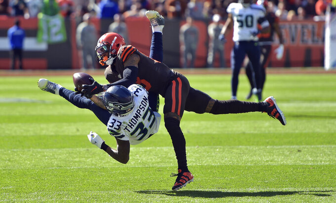Cleveland Browns wide receiver Odell Beckham Jr. (13) catches a pass under pressure from Seattle Seahawks free safety Tedric Thompson (33) during the first half of an NFL football game, Sunday, Oct. 13, 2019, in Cleveland. (AP Photo/David Richard)