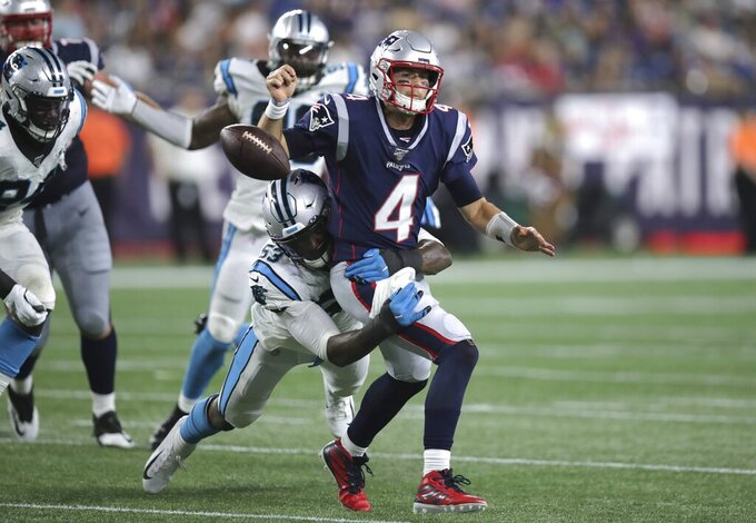 New England Patriots quarterback Jarrett Stidham (4) fumbles the ball as he is tackled by Carolina Panthers defensive end Brian Burns (53) in the second half of an NFL preseason football game, Thursday, Aug. 22, 2019, in Foxborough, Mass. (AP Photo/Charles Krupa)