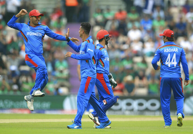 Afghanistan's Mujeeb Ur Rahman, center, celebrates taking the wicket of Bangladesh's Soumya Sarkar during the Cricket World Cup group stage match at The Hampshire Bowl, Southampton, England, Monday June 24, 2019. (Adam Davy/PA via AP)