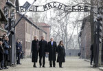 United States Vice President Mike Pence and his wife Karen Pence, right, stand with Poland's President Andrzej Duda and his wife Agata Kornhauser-Duda, left, under the gate during their visit at the Nazi concentration camp Auschwitz-Birkenau in Oswiecim, Poland, Friday, Feb. 15, 2019. The sign over the gate reads 'work makes one free'. (AP Photo/Michael Sohn)
